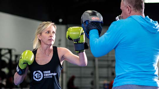 Woman wearing boxing gloves sparing with a man.