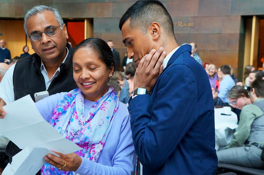 student and proud parents looking at match letter