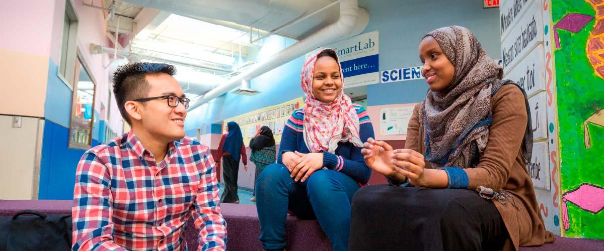 High school students Sabrina Ali  (middle) and Ramla Mohamud (right) ask their medical student mentor  Huy Donguyen about practical things like applying for scholarships and which classes to take to best prepare themselves for college.