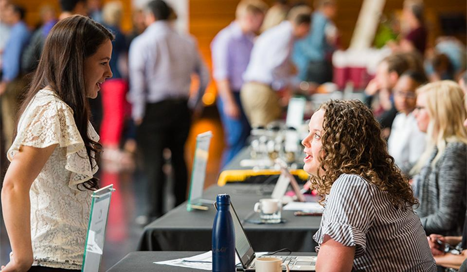 Trainee speaks to a staff member at a resource table during GME orientation