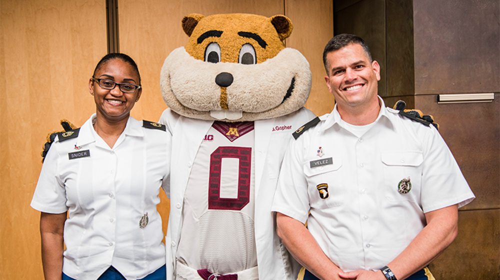Two US Army Medical Corps members pose with Goldy Gopher mascot