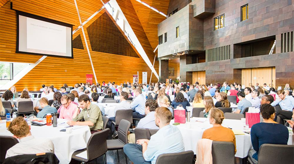 Trainees at round tables in the main hall of McNamara Alumni Center