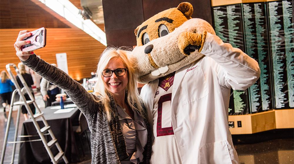 Woman taking a selfie with Goldy Gopher mascot